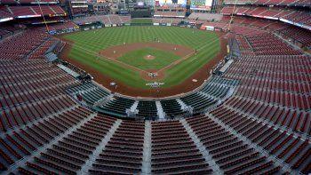 En esta imagen de archivo del 24 de julio de 2020, asientos vacíos en el estadio Busch de los Cardenales de San Luis, mientras el pitcher abridor Jack Flaherty lanza en el primer inning de su juego de béisbol contra los Piratas de Pittsburgh, en San Luis.