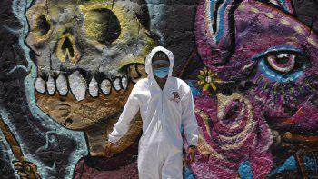 Un trabajador en el cementerio de San Nicolás Tolentino usa un traje de protección fuera del cementerio, en Iztapalapa, Ciudad de México, el jueves 30 de abril de 2020. Las autoridades han ordenado que todos los cuerpos de los que han muerto de COVID-19 deben ser cremados o enterrados con rapidez.