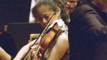 En esta foto del 14 de octubre de 2005, la violinista Midori toca con la Filarmónica de Nueva York, bajo la dirección de Marin Alsop, en el Lincoln Center en Nueva York.