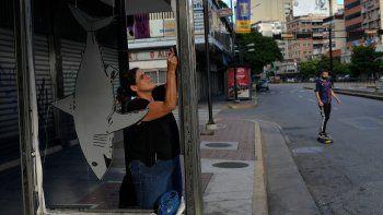 La artista Susan Applewhite coloca su obra de arte de cartón reciclado en una parada de autobús en el barrio Chacao de Caracas, Venezuela, el jueves 5 de noviembre de 2020.