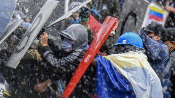 Manifestantes chocan con la policía antidisturbios durante una protesta contra el gobierno del presidente Iván Duque en la plaza Bolívar de Bogotá el 5 de mayo de 2021. Miles de personas regresaron a las calles de Colombia el miércoles en rechazo al gobierno de Iván Duque, quien ha cumplido una semana de presión con manifestaciones que se tornaron violentas en algunas ciudades y dejaron una veintena de muertos.