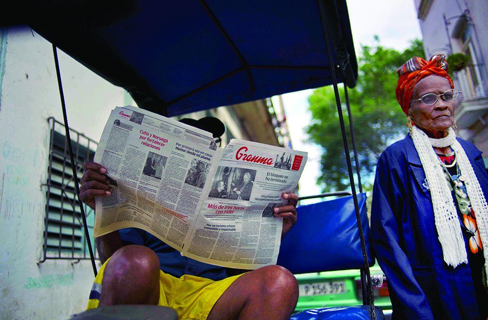 Un hombre lee el diario Granma que publicó las primeras fotos de Fidel Castro en casi seis meses