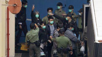 El exlegislador Leung Kwok-hung, 2do izquierda, hace una señal de victoria mientras llevan a varios de los 47 activistas por la democracia a la cárcel en Hong Kong, jueves 4 de marzo de 2021. Una corte se negó a otorgarles la libertad bajo fianza.