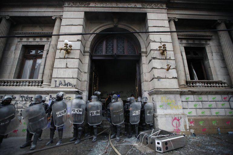 La policía antimotines forma un cordón mientras salen llamas de la sede del Congreso después de que manifestantes incendiaran una parte del edificio
