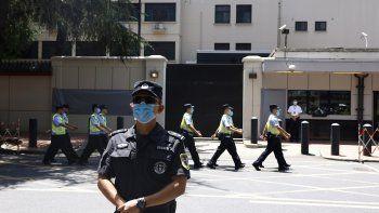 Policías chinos marchan ante el antiguo consulado estadounidense en Chengdu, en la provincia suroccidental china de Sichuan, el lunes 27 de julio de 2020.