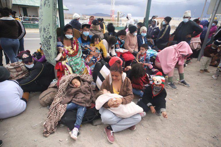 Los migrantes venezolanos se reúnen después de cruzar ilegalmente la frontera entre Bolivia y Chile en Colchane