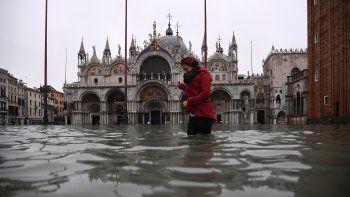 En esta foto de archivo tomada el 13 de noviembre de 2019, una mujer cruza la plaza de San Marcos inundada después de una marea alta excepcional durante la noche. Venecia evita la inclusión en la lista de sitios patrimoniales en peligro de extinción, anunció la Unesco el 22 de julio de 2021.