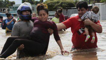 En esta fotografía de archivo del 5 de noviembre de 2020, una mujer embarazada es sacada de un área inundada por el agua traída por el huracán Eta en Planeta, Honduras. Los huracanes que han azotado Centroamérica han supuesto un fuerte obstáculo para la Organización Panamericana de la Salud y su lucha contra el COVID-19 ya que han dañado a más de 640 centros de salud, reducido al personal médico local y aumentado el riesgo de contagio en abarrotados refugios.