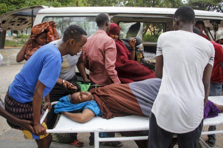 Trabajadores médicos y otros somalíes ayudan a una mujer que resultó herida cuando un coche bomba explotó frente al Hotel Elite