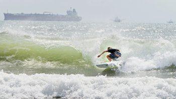 Un surfista se desplaza a orillas de la isla del Padre Sur el viernes 24 de julio de 2020 en medio de un mar picado debido a la tormenta tropical Hanna.