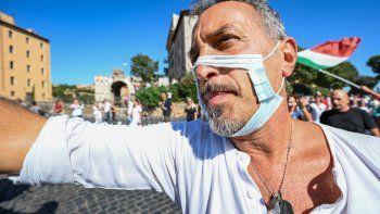 Un hombre con una mascarilla recortada participa en una protesta de los movimientos No Mask, movimientos negacionistas del COVID-19 movimientos anti-5G y movimientos anti-vacunación contra la política de salud del gobierno el 5 de septiembre de 2020 en Roma durante el COVID-19. Infección, causada por el nuevo coronavirus.