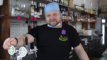 Cijay Brightman posa para una foto el 13 de julio del 2020 en el deli de Tel Aviv donde trabaja desde que estalló el brote de coronavirus y perdió su empleo como técnico de escenarios.