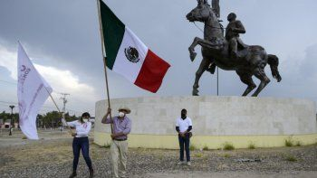 El candidato a alcalde independiente Julio González (C) ondea una bandera nacional mexicana durante un mitin de campaña en Dolores Hidalgo, estado de Guanajuato, México, el 5 de mayo de 2021. La violencia es desenfrenada en la campaña electoral local mexicana con varios candidatos asesinados o amenazados, como Julio González.
