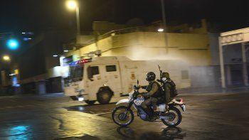 Miembros de la Guardia Nacional Bolivariana viajan en motocicleta mientras una tanqueta arroja desinfectante en las calles de Caracas, Venezuela, el sábado 21 de marzo de 2020.