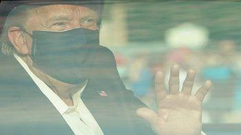 El presidente de los Estados Unidos, Donald Trump, saluda desde la parte trasera de un automóvil en una caravana fuera del Centro Médico Walter Reed en Bethesda, Maryland, el 4 de octubre de 2020.