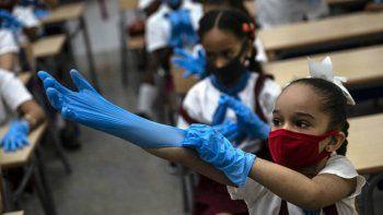 Una estudiante con máscara se pone guantes de plástico como medida de precaución en medio de la propagación del nuevo coronavirus durante una clase en La Habana, Cuba, el lunes 2 de noviembre de 2020. Decenas de miles de escolares regresaron a clases el lunes en La Habana por primera vez desde que la pandemia de coronavirus llevó a las autoridades a cerrar la isla en abril.