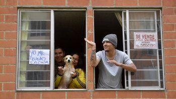 Vecinos de un edificio de apartamentos en Bogotá salen a las ventanas para participar en las clases de Zumba que imparte la Policía durante la cuarentena, el 8 de abril de 2020.