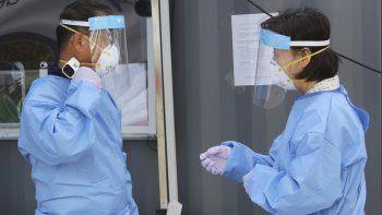 Un trabajador médico se mide la temperatura el miércoles 26 de agosto de 2020 en una clínica improvisada para realizar pruebas de COVID-19, en Seúl, Corea del Sur.