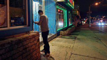En imagen de archivo del 12 de noviembre de 2020, un empleado del restaurante Justins BBQ, ubicado en una calle casi vacía, cierra el negocio en Newark, Nueva Jersey