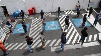 Personas mantienen sana distancia mientras esperan noticias de sus familiares, hospitalizados por COVID-19 a las afueras del Instituto de Seguridad Social hospital en Quito, Ecuador, el lunes 27 de julio de 2020