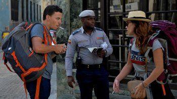 Un policía sostiene los pasaportes de dos turistas en La Habana, Cuba, luego del confinamiento obligatorio dictado por el régimen ante la propagación del coronavirus COVID-19.