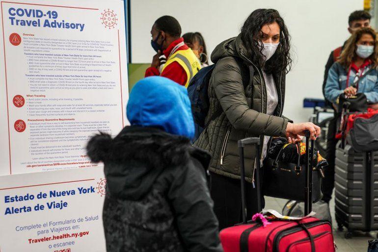 Varias personas portan mascarillas para evitar la propagación del COVID-19 mientras se preparan para abandonar la zona de entrega de equipaje en el Aeropuerto LaGuardia