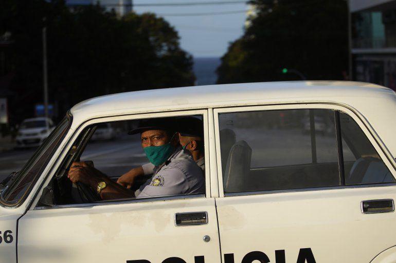 Agentes de policía con máscaras como precaución contra la propagación del nuevo coronavirus conducen una patrulla en una calle vacía durante el toque de queda en La Habana