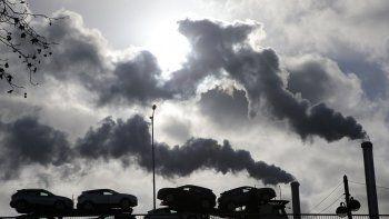 En esta imagen de archivo del viernes 30 de noviembre de 2018, humo saliendo de una fábrica mientras un camión cargado de autos pasa por un puente en París, Francia.