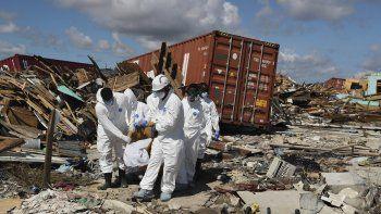 Forenses de Bahamas cargan un cuerpo el lunes 9 de septiembre de 2019 en el vecindario de El Lodazal en la zona de Marsh Harbor en la Isla Ábaco, en las Bahamas, tras el paso del huracán Dorian.