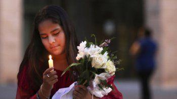 En esta imagen del 1 de septiembre de 2019, Jaxciri Solano enciende una vela y sostiene un ramo de flores al inicio de una vigilia en el campus de UTPB en Odessa, Texas, en memoria de las víctimas de un tiroteo el sábado.