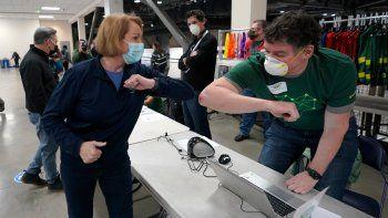En esta fotografía del 13 de marzo de 2021, la alcaldesa de Seattle, Jenny Durkan, saluda a un trabajador en un centro de vacunación, en Seattle, Washington.