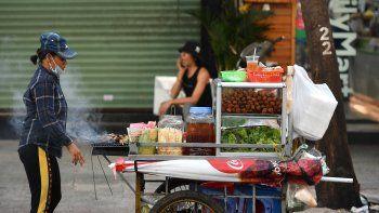 Esta fotografía tomada el 8 de septiembre de 2020 muestra a un vendedor ambulante de comida que vende rollitos de primavera y cerdo a la parrilla en la ciudad de Ho Chi Minh, Vietnam.