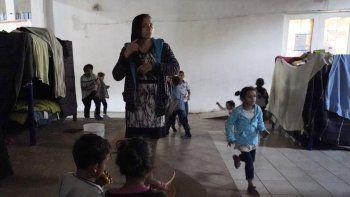 Una mujer hondureña que espera para entrar a Estados Unidos (centro), se peina mientras sus unos niños juegan cerca, en un albergue en Tijuana, México, el 17 de febrero de 2021.