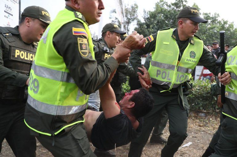 Miembros de la Policía de Colombia trasladan a un joven herido en los enfrentamientos con la PNB y los grupos paramilitares que actúan con la autorización del régimen.