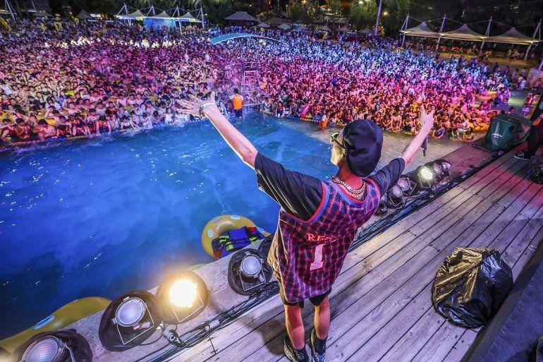 Esta foto tomada el 15 de agosto de 2020 muestra a personas que ven una actuación mientras se refrescan en una piscina en Wuhan