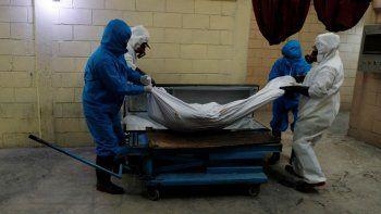 Trabajadores con trajes de protección levantan el cuerpo de una persona que murió de coronavirus antes de colocarlo en un horno de cremación en el cementerio Mausoleos San Cristóbal, en Ecatepec, Estado de México, al noreste de la Ciudad de México, el jueves 21 de mayo de 2020.