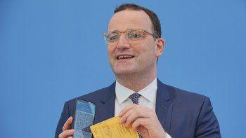 El ministro de Salud de Alemania, Jens Spahn, presenta la aplicación Corona Warn con un certificado digital de vacunación en la pantalla de su celular y su propio certificado de vacunación en la mano, durante una conferencia de prensa sobre la situación por el coronavirus, en Berlín, Alemania, el jueves 10 de junio de 2021.