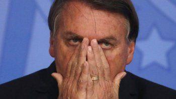 """El residente brasileño Jair Bolsonaro se pone las manos en el rostro durante una ceremonia en el palacio presidencial en Brasilia el jueves, 26 de noviembre del 2020. Bolsonaro dice que no va a vacunarse para el coronavirus y dijo que el uso de máscaras paralimitar la diseminación de la enfermedad es """"el último tabú en caer""""."""