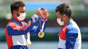 El medallista de oro de Cuba Serguey Torres Madrigal (der.) recibe la medalla de manos de su compañero de equipo Fernando Dayan Jorge Enríquez durante los Juegos Olímpicos de Tokio 2020