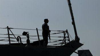 En esta foto del 12 de enero del 2012, un marinero estadounidense es visto junto a la bandera de Estados Unidos durante una ceremonia de cambio de comando a bordo del destructor USS Kidd, atracado en Muharraq, Bahréin.