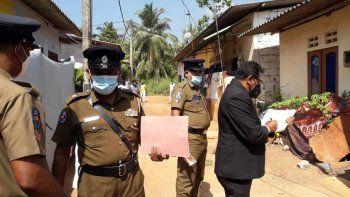 El magistrado de Sri Lanka Wasantha Ramanayake, a la derecha, y agentes de policía inspeccionan el exterior de una casa donde una niña de nueve años fue muerta en lata en Delgoda, Sri Lanka, el domingo 28 de febrero de 2021.