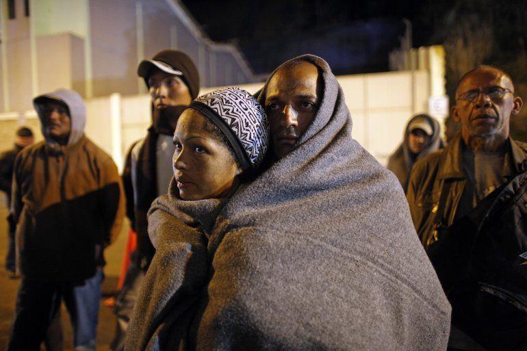 En esta imagen tomada el 5 de agosto del 2018 inmigrantes venezolanos en la frontera entre Colombia y Ecuador se tapan con una manta en un momento de su viaje hacia Perú.