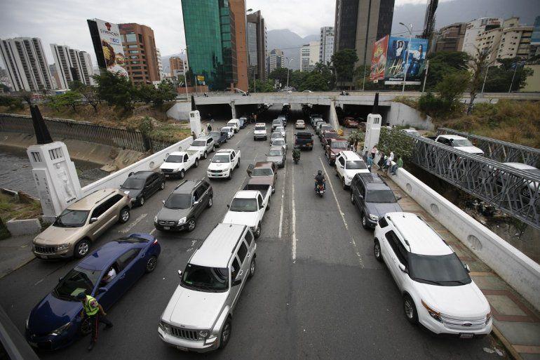 En esta foto de archivo del 29 de mayo de 2020 se observa a vehículos en fila cerca de una gasolinería para intentar llenar sus tanques en medio de una escasez de combustible en Caracas