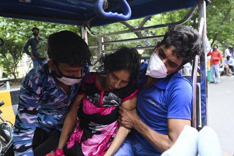 Un paciente se derrumba cuando lo llevan en un rickshaw en bicicleta fuera de un Gurudwara (Templo Sikh) que proporciona oxígeno gratis a los pacientes.