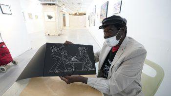 El artista conocido como Sir Shadow, que dibuja y exhibe su trabajo en espacios inmobiliarios vacíos, dibuja uno de sus dibujos característicos de un solo trazo el 25 de noviembre de 2020 en Nueva York.