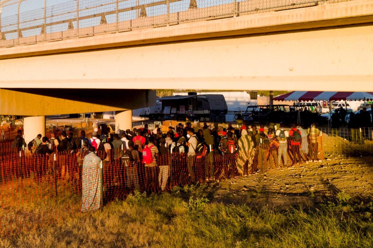 Migrantes, muchos procedentes de Haití, hacen fila el viernes 24 de septiembre de 2021 para subir a autobuses debajo del Puente Internacional de Del Rio, en Del Rio, Texas.