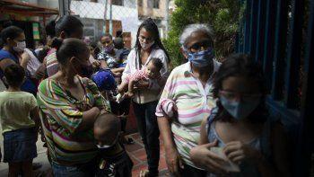 Varias mujeres y niños, con mascarillas para protegerse del coronavirus, aguardan su turno el viernes 20 de noviembre de 2020 durante una campaña de vacunación contra otras enfermedades organizada por el Ministerio de Salud, en el vecindario El Valle, en Caracas, Venezuela.