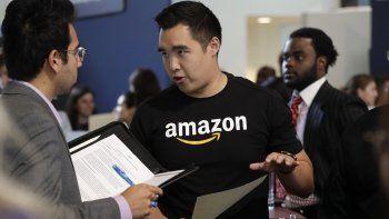 En esta fotografía del 17 de septiembre de 2019, el reclutador de Amazon Perry Chang habla con un prospecto durante una feria de trabajo realizada por la compañía.