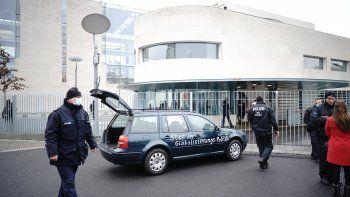 Un auto, parado delante de la cancillería tras estrellarse contra la valla de acceso al edificio donde está la oficina de Angela Merkel en Berlín, Alemania, el 25 de noviembre de 2020. La frase escrita sobre el auto dice: Paren la política de globalización.