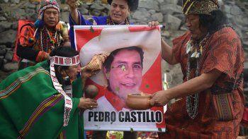 Los chamanes sostienen un cartel del candidato presidencial Pedro Castillo mientras realizan un ritual para predecir el ganador de la próxima segunda vuelta electoral en Perú